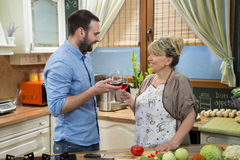 Smiling mother and son toasting with wine in the kitchen. Stock Image