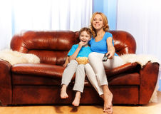 Smiling mother and son watch television at home Stock Photo