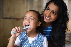 Smiling mother standing by daughter brushing teeth in bathroom Royalty Free Stock Images