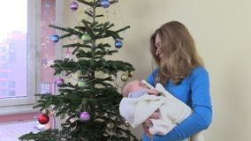 Smiling mother sway newborn baby in hands near Christmas tree stock video footage