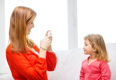Smiling mother taking picture of daughter Stock Photography