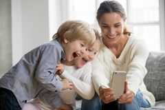 Smiling mother taking selfie with two cute kids on smartphone. Smiling mother taking selfie with cute kids on smartphone, happy young mom laughing making photo Stock Photo