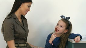 Smiling mother talking to her little girl eating a lollipop at doctor`s office stock video
