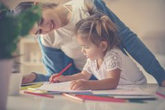 Mother teaching her daughter to drawing and writing at h. Smiling mother teaching her daughter to drawing and writing at home royalty free stock image