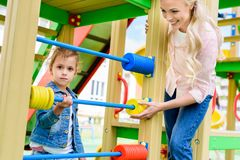 Smiling mother teaching to count little daughter on abacus at playground royalty free stock photo