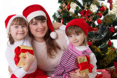 Smiling mother and two daughters under Christmas tree Royalty Free Stock Image