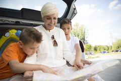 Smiling mother and two sons sitting with map in open car trunk. Beautiful smiling women and two boys sitting in open car trunk and looking at map Royalty Free Stock Photography