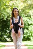 Smiling mother walking outdoors with baby in sling Royalty Free Stock Images