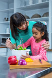 Smiling mother washing salad with her daughter royalty free stock photos