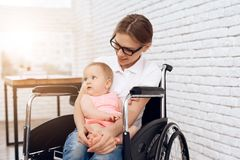 Smiling mother in wheelchair hugging newborn baby. royalty free stock image