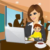 Smiling mother working on laptop in cafe Royalty Free Stock Photography