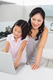 Smiling mother with young daughter using laptop in kitchen Royalty Free Stock Photography