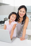 Smiling mother with young daughter using laptop in kitchen Stock Photos