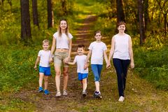 Smiling mothers and children holding hands. Big happy family, two women and three children in white t-shirts. Outdoors royalty free stock photo
