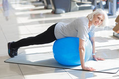 Smiling motivated woman training with fit ball. Favorite exercise. Inspired beautiful senior woman using fit ball and smiling while having workout in a gym Stock Photo