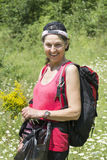 Smiling mountaineer woman with backpack. Happy mountaineer woman with bouquet of herbs in the hand royalty free stock photo