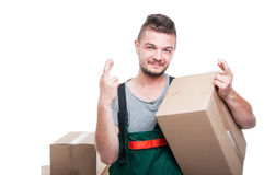Smiling mover guy holding cardboard box showing fingers crossed Stock Photo