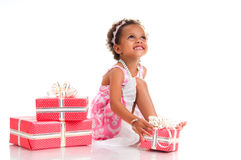 Smiling mulatto girl with pink gift box. Birthday present. Royalty Free Stock Image