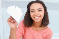 Smiling mulatto girl throwing paper plain Stock Photo