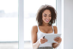 Smiling mulatto woman holding tablet Royalty Free Stock Photos