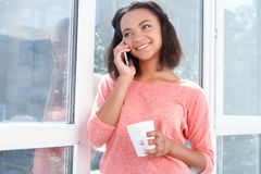 Smiling mulatto woman talking per cell phone Royalty Free Stock Photography