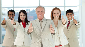 Smiling multi-ethnic business team with thumbs up Stock Images