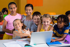 Smiling multi ethnic children using laptop. Portrait of smiling multi ethnic children using laptop in clasroom royalty free stock photos