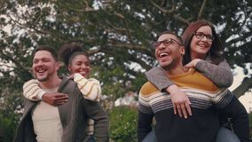 Smiling multi-ethnic couples having fun by carrying their girlfriends on piggyback ride in the park. Happy men carrying their girlfriends piggyback in park stock video
