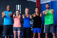 Smiling multi-ethnic friends showing thumbs up in gym. Portrait of smiling multi-ethnic friends showing thumbs up while standing in gym Royalty Free Stock Image