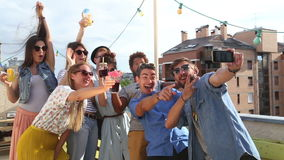 Smiling multi-ethnic friends taking selfie on the rooftop terrace. Group of smiling multi-ethnic friends taking selfie on the rooftop terrace stock video