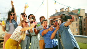Smiling multi-ethnic friends taking selfie on the rooftop terrace. Group of smiling multi-ethnic friends taking selfie on the rooftop terrace, graded stock video footage