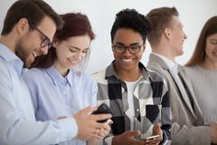 Smiling multi-ethnic people holding phones having fun with mobile devices. Happy friendly young diverse people using smartphones social media applications taking stock photography