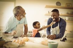 Multi-generation family with flour on the nose standing in the kitchen stock photos