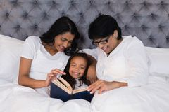 Smiling multi-generation family reading book while resting on bed Stock Image
