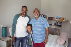 Smiling multi-generation family standing together in bedroom. Portrait of smiling multi-generation family standing together in bedroom stock photos