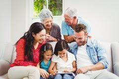 Smiling multi generation family using digital tablet Stock Image