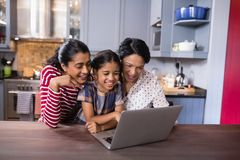 Smiling multi-generation family using laptop in kitchen Stock Photography