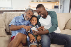 Smiling multi-generation family using mobile phone in living room. At home stock photography