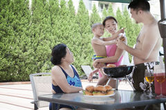 Smiling multi-generational family barbequing by the pool on vacation Royalty Free Stock Photography