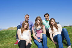 Smiling, Multi-racial group of Young Adults. A group of young friends sitting together outside. A multi-racial, attractive group of Young adults Stock Photography