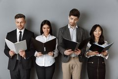 Smiling multicultural business people with folders and notebooks waiting. For job interview stock image