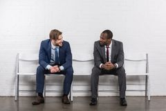 Smiling multicultural businessmen looking at each other while waiting. For job interview stock photography