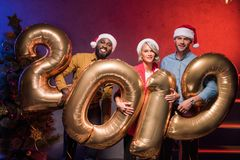 Smiling multicultural businesspeople holding 2019 balloons at new year. Corporate party stock photos