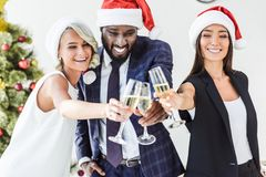Smiling multicultural businesspeople in santa hats clinking with glasses of champagne. In office royalty free stock photo