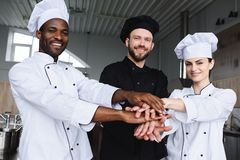 Smiling multicultural chefs putting hands together. At restaurant kitchen royalty free stock photo