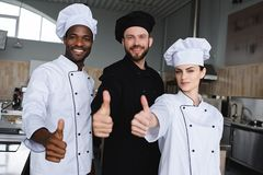 Smiling multicultural chefs showing thumbs up. At restaurant kitchen stock images