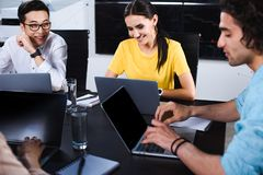 Smiling multicultural group of business partner talking at table with laptops in modern. Office stock photography