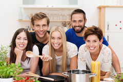 Smiling multicultural group of friends cooking royalty free stock photo