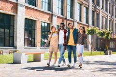 Smiling multicultural group of friends hugging while walking. On street together stock photos