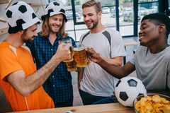 Smiling multicultural group of male football fans clinking beer glasses during watch of soccer match. At bar royalty free stock photo